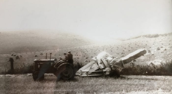 Harvest at Hunmanby Grange in the 1940s/50s. An open cab tractor pulls along an early style combine. Very different from present day combines!